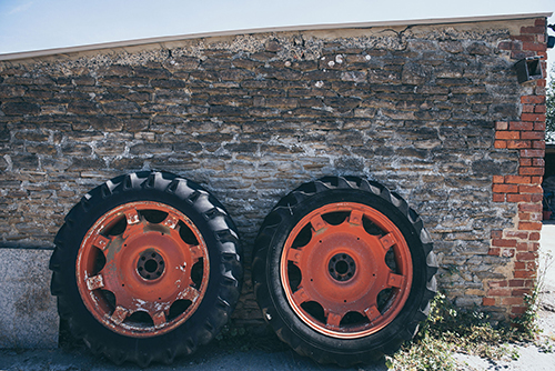 An image of two tractor wheels up against a brick wall